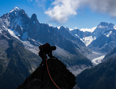 Climber in the Aiguilles Rouge. The Aiguille Vert, The Dru, The Grand Jorasses and the Mer de Glace in the background. Chamonix, France.