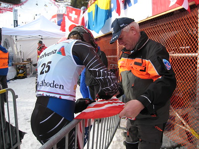 Jimmy Cochran signs an American flag for a fan at Adelboden  (credit: Doug Haney/U.S. Ski Team)