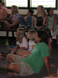 Erik Schlopy (Park City, UT) listens to his teammates talk about ski racing with children from the Sugarhouse Boys & Girls Club in Salt Lake City (July 23, 2007). Children in top row (l to r): Mattelynn Plavchak, Carlos Haycok, Wendy Petro, Vatasana Stram. Children next to Schlopy (l to r): Kamarin Barclay, Lauren Angell. Photo credit: Juliann Fritz/USSA