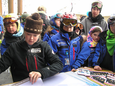 Kaylin Richardson of the U.S. Ski Team signs autographs for a pack of young fans at the 60th birthday party for Coronet Peak Ski Area in New Zealand (credit: Coronet Ski Area)