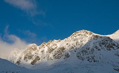 The morning sun strikes first light on a snow-covered mountain range high above Soelden, Austria. (c) 2009 Tom Kelly