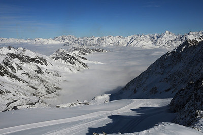 Pillowy clouds blanket the valley as towering Tyrolean alpine peaks ring the area around Soelden, Austria as seen from the Rettenbach Glacier. (c) 2009 Tom Kelly