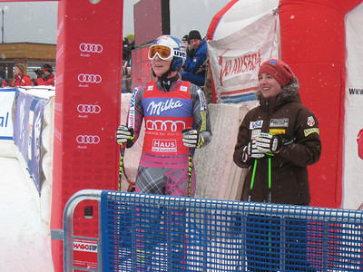Lindsey Vonn and Stacey Cook watch the big screen as teammate Julia Mancuso burns to an 11th place finish in the second Haus im Ennstal downhill (Doug Haney/U.S. Ski Team)
