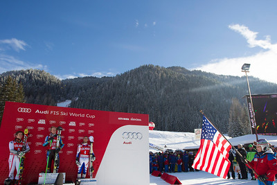 ALTA BADIA, ITALY - DECEMBER 16: Marcel Hirscher of Austria (L) 2nd placed racer and Ted Ligety of USA (C) winner and Thomas Fanara of France (R) 3rd placed racer on the podium as a local child waves a US flag, during the prize giving ceremony for the Audi FIS Alpine Ski World Cup Giant Slalom race on December 16 2012 in Alta Badia, Italy. (Photo by Mitchell Gunn/ESPA) Image may be used for editorial use only.