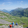 Hikers having a rest. This is an excellent view of the Kiental valley, overlooking Griesalp. Far in the distance, you can see Lake Thun.