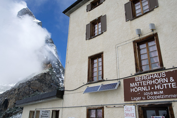 Hornli hut with the Matterhorn peeking from the clouds behind.