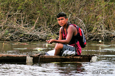 """©Al Gallia; """"Fisherman in Belize""""; Indigenous fisherman (probably Mestizo or Mayan) hand line fishing in dugout canoe on the New River in Belize, near the Lamanai Mayan Ruins."""