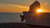 Rising Sun, Diagonal Cloud, and Boat on Beach