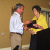 Aleita Sullivan presents Bill May a plaque thanking him for his service as President of the Law Alumni Chapter