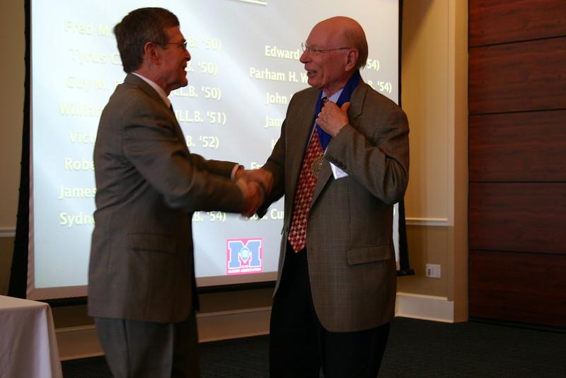 Dean Sam Davis presents a medallion to former law dean Parham Williams (LL.B. 54)