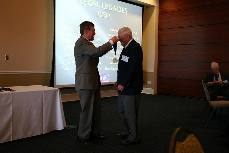 Dean Sam Davis presents a medallion to Jim McClure (LL.B. 53)