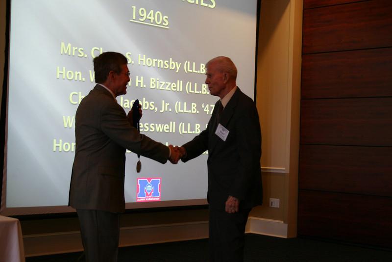 Dean Sam Davis presents a medallion to Hon. Bill Bizzell (LL.B. 47)