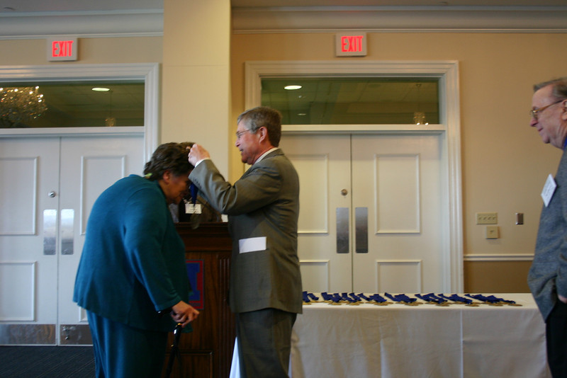 Dean Sam Davis presents a medallion to Sylvia McDavid (LL.B. 56)
