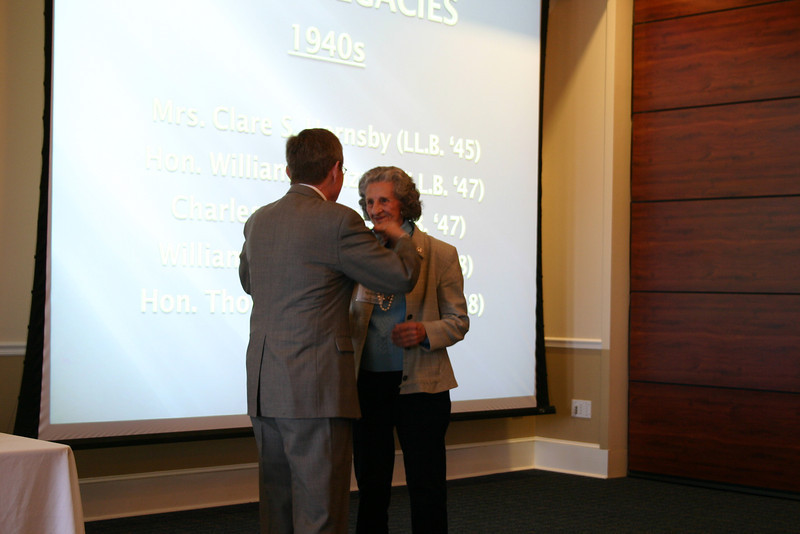 Dean Sam Davis presents a medallion to Clair Hornsby (LL.B. 45)