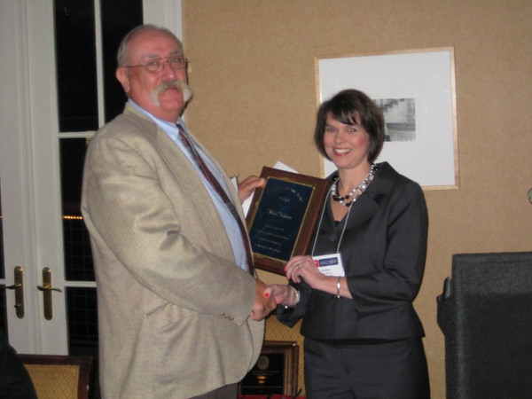 Dr. Donna West Strum presents the Pharmacy Administration Alumnus of the Year Award to Dr. Mick Kolassa (Ph.D. 95)
