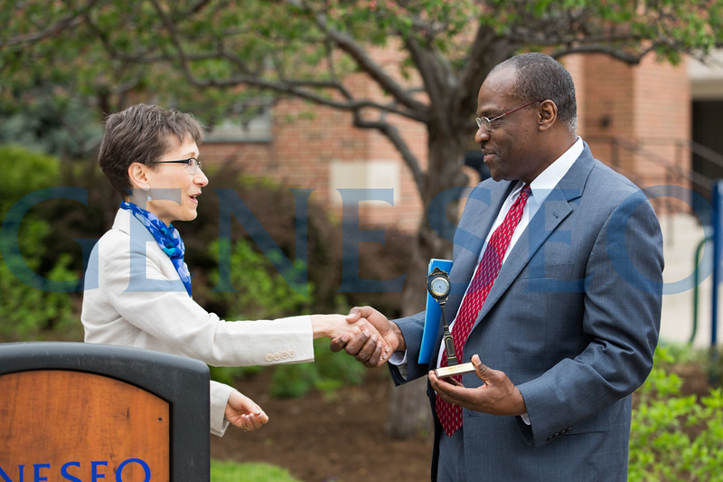 President Denise Battles shakes Enrico Johnson's hand as he accepts an award on behalf of Mark Scott and CAS