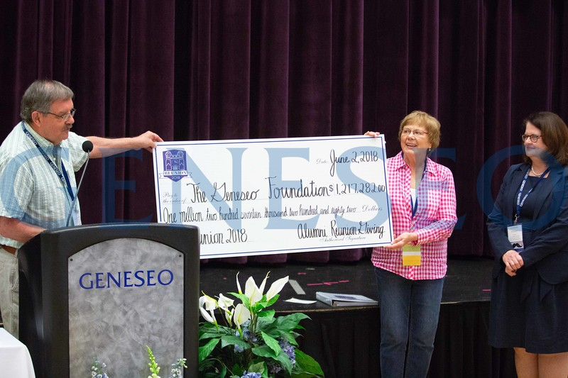 Bob '67 and Nancy '68 Hussey present Johnson Bowles with the alumni giving check