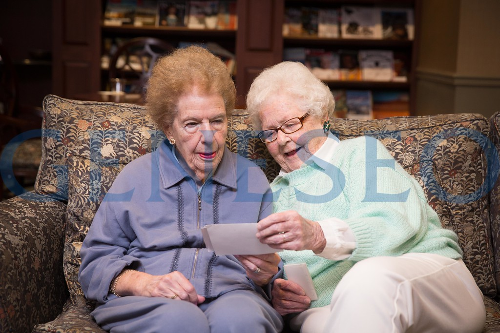 Joanne Siegel (left) and Eleanor (Bonnet) Betlem reminisce over photographs KW Fall 2017