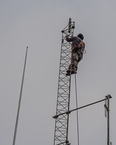 Cesar Alvarez, KD6BHJ, at the top of the tower preparing to install a new antenna