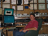 Joel Harrison W5ZN in his partially rebuilt shack.  To our left are the computers for the Flex 5000,  Great Circle map, logging software,  Flex 5000.  His M2 rotator boxes are above his shoulder.  Ft920 and FT1000 MkV, and behind him is another FT920, FT847.   His new transverters (2m and 220) from DownEast  are above the radios.