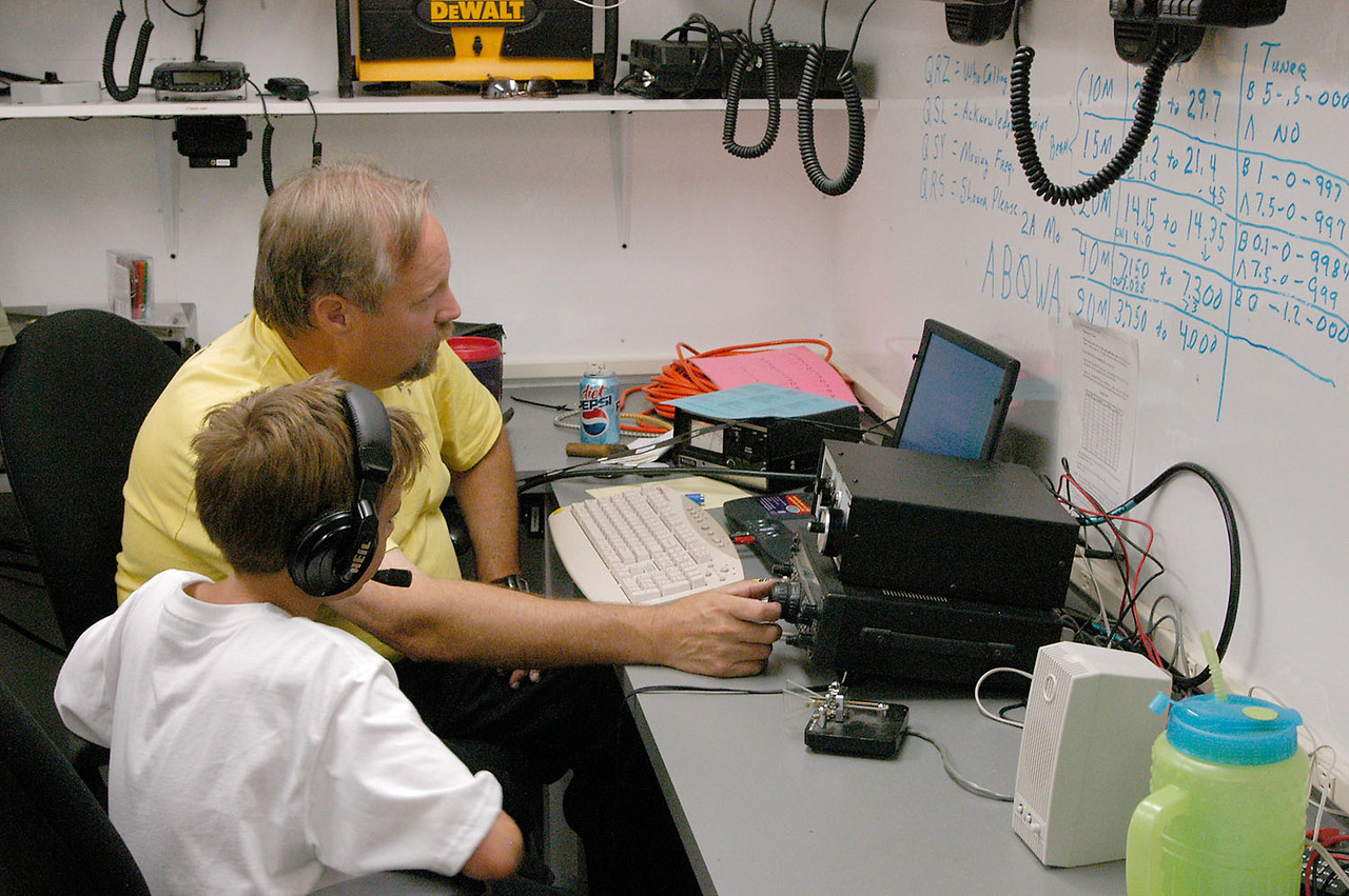 KC0ELZ helps a young operator get on the air from the GOTA station. - <i>Sunday, morning</i>