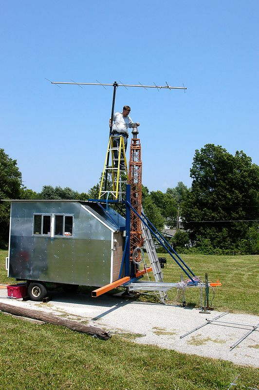 KC0DDZ getting ready to put the mast (with 2m beam already mounted) on the tower of the UHF/VHF station. The UHF/VHF station was setup inside KC0DDZ's home built trailer. Nice work Paul! - <i>Friday, mid-day</i>