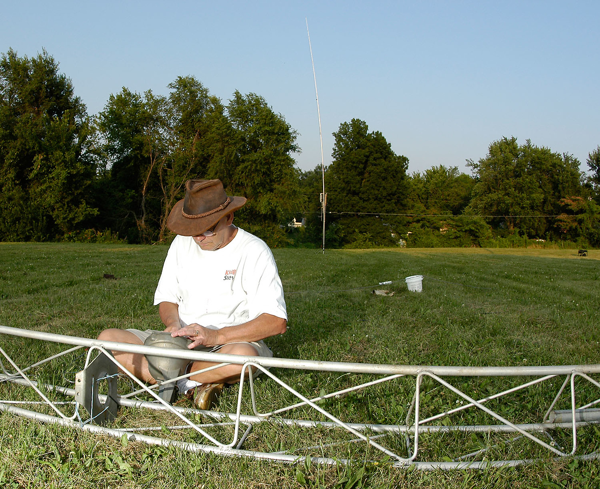 K0OU working on the rotator for the CW tower. The CW station's vertical antenna is visible in the background. - <i>Friday, early evening</i>