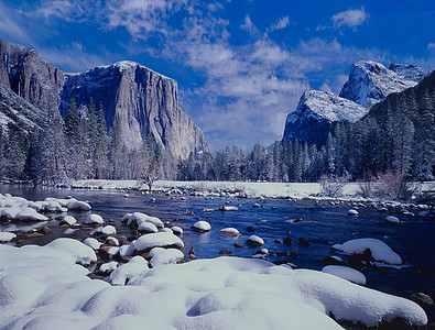 The Merced River flows through the Yosemite Valley floor as  a clearing Winter Storm leaves a blanket of fresh snow in Yosemite Nat'l Park with El Capitan and Cathedral Peaks in the background.