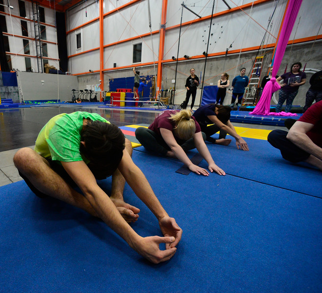 KRISTOPHER RADDER — BRATTLEBORO REFORMER<br /> Chris Mays, a reporter from the Brattleboro Reformer, stretches before learning how to go on silks and a trapeze during an open class at the New England Center of Circus Arts on Monday, Feb. 17, 2020.