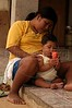 Joelma Cinta Larga, 19, sits in front of her home with her 8 month baby on the the Roosevelt Indian Reserve near Espigao D'oeste in Brazil's western state of Rondonia, Oct. 28, 2004, about 2,100 miles northwest of Rio de Janeiro. Many believe the reservation holds South America's largest diamond lodes and could possibly pay Brazil's foreign debt, which has lead to a diamond rush on and around Indian lands. In April 2004, Indians from the Cinta Larga tribe killed 29 illegal diamond diggers inside their reservation. The massacre increased tensions between Indians and miners, and federal police since have stationed about 50 officers near the reservation, and conduct raids on nearby mines. (AustralFoto/Douglas Engle)