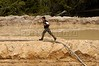 A Brazilian Federal Police runs through a diamond mine during a raid near Espigao D'oeste in the western state of Rondonia, Oct. 28, 2004, about 2,100 miles northwest of Rio de Janeiro. The region, which borders on the Roosevelt Indian Reservation, has seen a Diamond rush recently, some of which has encroached on Indian lands. In April 2004, Indians from the Cinta Larga tribe killed 29 illegal diamond diggers inside their reservation. The massacre increased tensions between Indians and miners, and federal police since have stationed about 50 officers near the reservation, and conduct raids on nearby mines. Many believe the reservation holds South America's largest diamond lodes and could possibly pay Brazil's foreign debt.(AustralFoto/Douglas Engle)