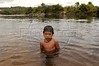A Cinta Larga Indian boy swims in the Roosevelt River, named after US president Theodore Roosevelt, on the the Roosevelt Indian Reserve near Espigao D'oeste in Brazil's western state of Rondonia, Oct. 28, 2004, about 2,100 miles northwest of Rio de Janeiro. Many believe the reservation holds South America's largest diamond lodes and could possibly pay Brazil's foreign debt, which has lead to a diamond rush on and around Indian lands. In April 2004, Indians from the Cinta Larga tribe killed 29 illegal diamond diggers inside their reservation. The massacre increased tensions between Indians and miners, and federal police since have stationed about 50 officers near the reservation, and conduct raids on nearby mines. (AustralFoto/Douglas Engle)