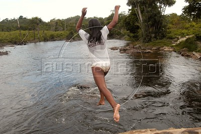 A Cinta Larga Indian girl jumps from a bridge into the Roosevelt River, named after US president Theodore Roosevelt, on the the Roosevelt Indian Reserve near Espigao D'oeste in Brazil's western state of Rondonia, Oct. 28, 2004, about 2,100 miles northwest of Rio de Janeiro. Many believe the reservation holds South America's largest diamond lodes and could possibly pay Brazil's foreign debt, which has lead to a diamond rush on and around Indian lands. In April 2004, Indians from the Cinta Larga tribe killed 29 illegal diamond diggers inside their reservation. The massacre increased tensions between Indians and miners, and federal police since have stationed about 50 officers near the reservation, and conduct raids on nearby mines. (AustralFoto/Douglas Engle)