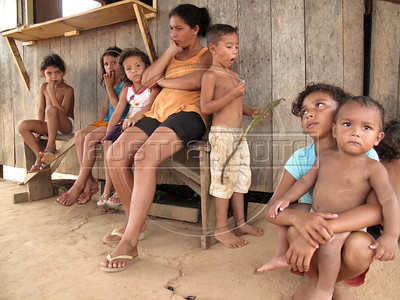Maria Selma da Costa sits with her children and nephews and nieces  near Caapiranga in the Brazilian state of Amazonas, Nov. 4, 2010. da Costa and other residents of Caapiranga are feeling the effects of the record drought in the region as goods and services have virtually stopped arriving in the town town which is only accessable yr river or air.  River levels broke the previous drought record which was set only 5 years ago, a frequency which environmental groups say are a direct result of deforestation and global warming. (Australfoto/Douglas Engle)