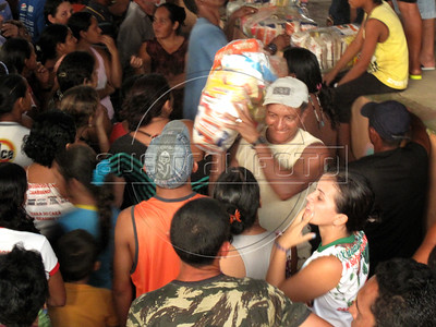 """Residents of Caapiranga, which is only accessable by river or air, get """"basic baskets"""" of food supplies in the Brazilian state of Amazonas, Nov. 4, 2010. The low river levels broke the previous drought record which was set only 5 years ago, a frequency which environmental groups say are a direct result of deforestation and global warming. (Australfoto/Douglas Engle)"""