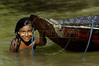 A girl plays near a wooden canoe in the Balique island arquipelago of the Amazon river delta of Brazil's northern Amapa state, Dec. 6, 2004. The village is served every two months by a boat carrying some 40 people from the justice department and other state agencies who travel 12 hours from the state capital Macapa, in an effort to include the population in the state system. It is a unique Brazilian solution to the immense geography of the Amazon, where roads do not exist and travel is costly and slow. People who once lived their whole lives with no records of birth, mariage, death, or even ID cards, are no longer forgotton by the state in this real life waterworld. (AustralFoto/Douglas Engle)