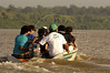 """Members of the Amapa state justice department, leave the """"Tribuna"""" coartroom boat in a motorboat to reach a community along a shallow river, where larger boats cannot enter, in the Balique island arquipelago of the Amazon river delta of Brazil's northern Amapa state. Every two months some 40 people from the justice department and other state agencies travel from the state capital Macapa down the Amazon river in a mission to bring state services to residents of the remote region. It is a unique Brazilian solution to the immense geography of the Amazon, where roads do not exist and travel is costly and slow. People who once lived their whole lives with no records of birth, mariage, death, or even ID cards, are no longer forgotton by the state in this real life waterworld. (AustralFoto/Douglas Engle)"""