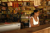 """Reginalda Selvatica at the counter of her small shop in the """"Terra do Meio"""" or Middle Lands, in the municipality of Sao Felix do Xingu in Brazil's Amazonian state of Para. Named for the area between the Xingu and Iriri Rivers, the 29,343 sq. mile area (slightly smaller than Maine or Scotland) lies in the path of progress as cattle ranches encroach from the east and big business soy advances from the south. illegal logging, labor, land-grabbing and human rights abuses in the area are not uncommon. Simple people, looking for opportunity to have some cheap land, are migrating to the reagion. Much Like the favelas of Rio de Janeiro, which were not officially included on city maps until the mid-1990s, the Middle Land is also a species of autonomous zone - a black hole of information and uncertainty over which Brazilian authorities in reality have little control. (AustralFoto/Douglas Engle)"""