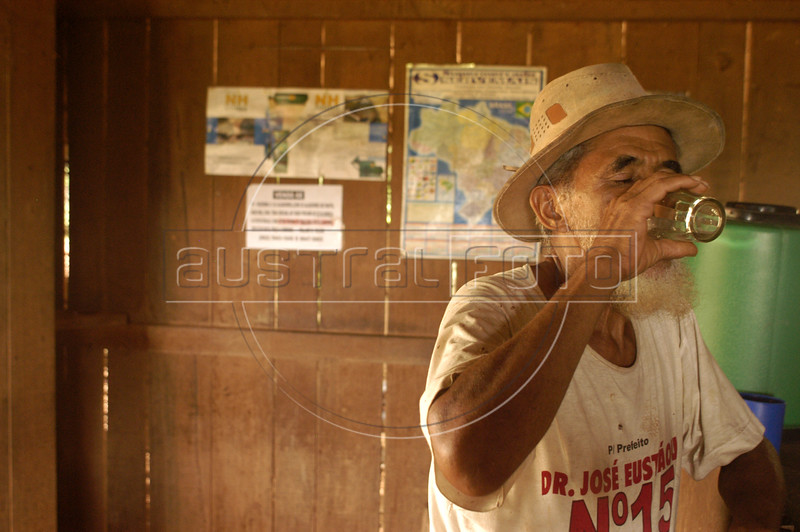 """A man drinks Cachaca, Brazi's favorite cane-liquor in the """"Terra do Meio"""" or Middle Lands, in the municipality of Sao Felix do Xingu in Brazil's Amazonian state of Para. Named for the area between the Xingu and Iriri Rivers, the 29,343 sq. mile area (slightly smaller than Maine or Scotland) lies in the path of progress as cattle ranches encroach from the east and big business soy advances from the south. illegal logging, labor, land-grabbing and human rights abuses in the area are not uncommon. Simple people, looking for opportunity to have some cheap land, are migrating to the reagion. Much Like the favelas of Rio de Janeiro, which were not officially included on city maps until the mid-1990s, the Middle Land is also a species of autonomous zone - a black hole of information and uncertainty over which Brazilian authorities in reality have little control. (AustralFoto/Douglas Engle)"""