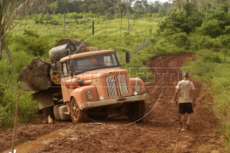 """Like nature's last revenge, a timber truck get stuck in the mud In the """"Terra do Meio"""" or Middle Lands, in the municipality of Sao Felix do Xingu in Brazil's Amazonian state of Para. Named for the area between the Xingu and Iriri Rivers, the 29,343 sq. mile area (slightly smaller than Maine or Scotland) lies in the path of progress as cattle ranches encroach from the east and big business soy advances from the south. illegal logging, labor, land-grabbing and human rights abuses in the area are not uncommon. Simple people, looking for opportunity to have some cheap land, are migrating to the reagion. Much Like the favelas of Rio de Janeiro, which were not officially included on city maps until the mid-1990s, the Middle Land is also a species of autonomous zone - a black hole of information and uncertainty over which Brazilian authorities in reality have little control. (AustralFoto/Douglas Engle)"""