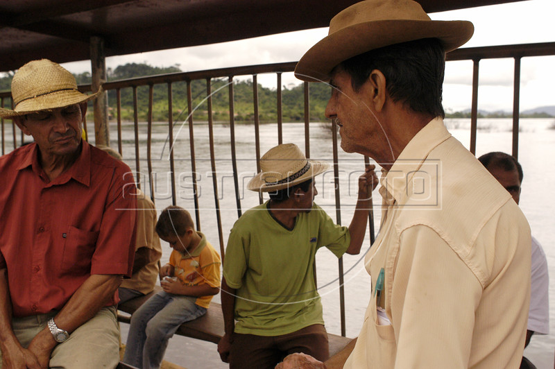 """Ferry passengers cross the Xingu River to the """"Terra do Meio"""" or Middle Lands, in the municipality of Sao Felix do Xingu in Brazil's Amazonian state of Para. Named for the area between the Xingu and Iriri Rivers, the 29,343 sq. mile area (slightly smaller than Maine or Scotland) lies in the path of progress as cattle ranches encroach from the east and big business soy advances from the south. illegal logging, labor, land-grabbing and human rights abuses in the area are not uncommon. Simple people, looking for opportunity to have some cheap land, are migrating to the reagion. Much Like the favelas of Rio de Janeiro, which were not officially included on city maps until the mid-1990s, the Middle Land is also a species of autonomous zone - a black hole of information and uncertainty over which Brazilian authorities in reality have little control. (AustralFoto/Douglas Engle)"""
