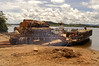 """A log truck embarks on a ferry to cross the Xingu River, leaving the """"Terra do Meio"""" or Middle Lands, in the municipality of Sao Felix do Xingu in Brazil's Amazonian state of Para. Named for the area between the Xingu and Iriri Rivers, the 29,343 sq. mile area (slightly smaller than Maine or Scotland) lies in the path of progress as cattle ranches encroach from the east and big business soy advances from the south. illegal logging, labor, land-grabbing and human rights abuses in the area are not uncommon. Simple people, looking for opportunity to have some cheap land, are migrating to the reagion. Much Like the favelas of Rio de Janeiro, which were not officially included on city maps until the mid-1990s, the Middle Land is also a species of autonomous zone - a black hole of information and uncertainty over which Brazilian authorities in reality have little control. (AustralFoto/Douglas Engle)"""