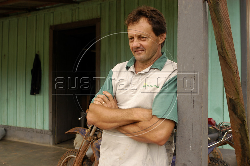 """Wantuil Selvatico stands outside his small shop in the """"Terra do Meio"""" or Middle Lands, in the municipality of Sao Felix do Xingu in Brazil's Amazonian state of Para. Named for the area between the Xingu and Iriri Rivers, the 29,343 sq. mile area (slightly smaller than Maine or Scotland) lies in the path of progress as cattle ranches encroach from the east and big business soy advances from the south. illegal logging, labor, land-grabbing and human rights abuses in the area are not uncommon. Simple people, looking for opportunity to have some cheap land, are migrating to the reagion. Much Like the favelas of Rio de Janeiro, which were not officially included on city maps until the mid-1990s, the Middle Land is also a species of autonomous zone - a black hole of information and uncertainty over which Brazilian authorities in reality have little control. (AustralFoto/Douglas Engle)"""