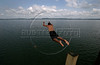 A boy jumps from the pier into the Tapajos River in Fordlandia, a former factory town created by the Ford Motor Company, September 6, 2005. Deep in the Amazon forest, 12 hours by boat from the regional capital of Santarem in Brazil's Par‡a state, the rubber plantation and processing factory is now abandoned to the rain-forest, an aging memorial to American ideals and to the Brazilian reality. It almost seems like time has stopped in Fordlandia, or better yet, time has passed it by. In typical american style, it was organized and efficient, an idea admired by many Brazilians, and perhaps more so by residents of the untamed Amazon. But It is an idea hard to implement in the wilds of the amazon. Some might also say that it is also a typical American style the way Ford came here and tried to implement something with little knowledge of the local customs or terrain. From 1928 to 1945, Ford came tried to take control of his rubber supply, one of the most important products of the rainforest. After only 17 years the company admitted defeat and retreated from the forest. (AustralFoto/Douglas Engle)