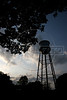 The trademark American water tower is seen in Fordlandia, a former factory town created by the Ford Motor Company on the banks of the Tapaj—os River, September 6, 2005. Deep in the Amazon forest, 12 hours by boat from the regional capital of Santarem in Brazil's Par‡a state, the rubber plantation and processing factory is now abandoned to the rain-forest, an aging memorial to American ideals and to the Brazilian reality. It almost seems like time has stopped in Fordlandia, or better yet, time has passed it by. In typical american style, it was organized and efficient, an idea admired by many Brazilians, and perhaps more so by residents of the untamed Amazon. But It is an idea hard to implement in the wilds of the amazon. Some might also say that it is also a typical American style the way Ford came here and tried to implement something with little knowledge of the local customs or terrain. From 1928 to 1945, Ford came tried to take control of his rubber supply, one of the most important products of the rainforest. After only 17 years the company admitted defeat and retreated from the forest. (AustralFoto/Douglas Engle)