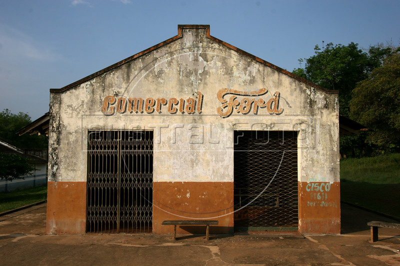A store uses the name of the auto maker in Fordlandia, a former factory town created by the Ford Motor Company on the banks of the Tapaj—os River, September 6, 2005. Deep in the Amazon forest, 12 hours by boat from the regional capital of Santarem in Brazil's Para‡ state, the rubber plantation and processing factory is now abandoned to the rain-forest, an aging memorial to American ideals and to the Brazilian reality. It almost seems like time has stopped in Fordlandia, or better yet, time has passed it by. In typical american style, it was organized and efficient, an idea admired by many Brazilians, and perhaps more so by residents of the untamed Amazon. But It is an idea hard to implement in the wilds of the amazon. Some might also say that it is also a typical American style the way Ford came here and tried to implement something with little knowledge of the local customs or terrain. From 1928 to 1945, Ford came tried to take control of his rubber supply, one of the most important products of the rainforest. After only 17 years the company admitted defeat and retreated from the forest. (AustralFoto/Douglas Engle)