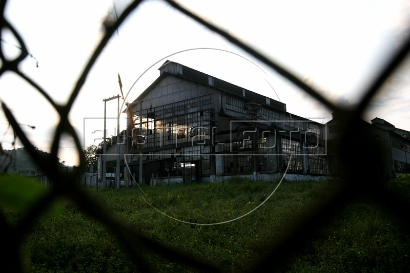 A factory building is seen through a fence in Fordlandia, a former factory town created by the Ford Motor Company on the banks of the Tapaj—os River, September 6, 2005. Deep in the Amazon forest, 12 hours by boat from the regional capital of Santarem in Brazil's Para‡ state, the rubber plantation and processing factory is now abandoned to the rain-forest, an aging memorial to American ideals and to the Brazilian reality. It almost seems like time has stopped in Fordlandia, or better yet, time has passed it by. In typical american style, it was organized and efficient, an idea admired by many Brazilians, and perhaps more so by residents of the untamed Amazon. But It is an idea hard to implement in the wilds of the amazon. Some might also say that it is also a typical American style the way Ford came here and tried to implement something with little knowledge of the local customs or terrain. From 1928 to 1945, Ford came tried to take control of his rubber supply, one of the most important products of the rainforest. After only 17 years the company admitted defeat and retreated from the forest. (AustralFoto/Douglas Engle)