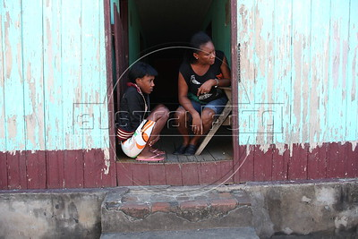 Silvaine Doris, 46, mother of 2 from Môle-Saint-Nicolas, Haiti, right, and another Haitian woman wait outside a small hotel in Brasileia, in Brazil's Amazonian state of Acre, on the border with Bolivia. Hundreds, if not thousands, of Haitians are showing up in Brazil - after an odyssey through Equador, Peru and Bolivia - with hopes of gaining residency as refugees in South America's largest nation. (Douglas Engle/Australfoto)