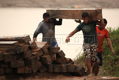 Workers unload wood from a boat at the port in Boca do Acre, Amazonas state, Brazil, May 10, 2011, where most, if not all, of the wood is considered illegal by Brazilian authorities. Although deforestation in the Braziian Amazon has decreased overall, Amazonas state has seen a 91% increase in forest clearing, according to data from the Brazilian Space Research Institute (INPE). Boca do Acre, named for its location at the mouth of the Acre River in southern Amazonas state in Brazil, led the state during the data collection period of Aug. 2010-Feb. 2011. Residents say the only road leading to the city - 200km long, partially paved, and lined with cattle ranches - used to pass through dense forest, which can only be seen at a distance or at parts which pass through an Indigenous reservation. (Douglas Engle/Australfoto)