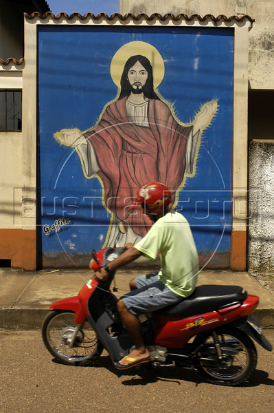 A motorcycle passes a mural of Christ on a wall in Altamira, an Amazonian frontier capital in the Brazilian state of Para. The town on the Trans-amazonian highway is a hotbed for illegal logging, labor, land-grabbing and human rights abuses as ranchers and loggers resort to extremes in their advance on the Amazon forest. Ever since the murder of 73-year-old American nun Dorothy Stang in February 2005, the Catholic Bishop of Altamira, Austrian-born Erwin Krautzer, 68, has been under armed guard. But Stang, an adamant defender of the poor in the Amazon,  probably did more in death than in life to help them - her murder brought worldwide attention to the region and in the aftermath, the federal government has created environmental reserves and established a Federal Police office.(AustralFoto/Douglas Engle)